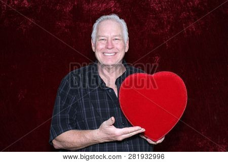 Valentines Day. A handsome man holds a Red Velvet Valentines Day Box of Chocolates. Romantic Valentines Day. Room for text.