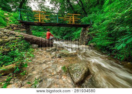Man Doing Yoga Beside Waterfall - Wooden Bridge Over Waterfall In Himalayas - Sainj, Kullu, Himachal