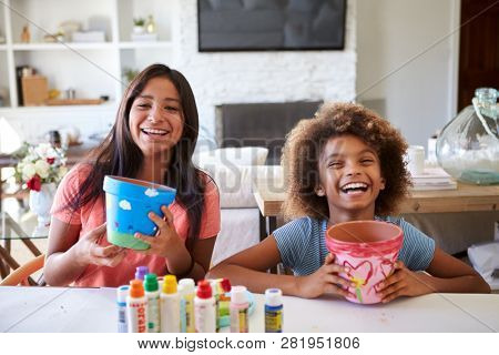 Happy pre-teen girl and her older girlfriend holding plant pots that they've decorated with paints at home, smiling to camera, close up