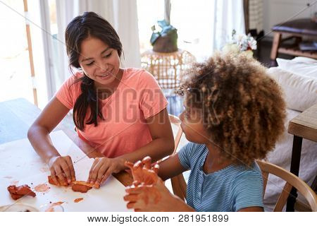 Two young teen and pre-teen girlfriends sitting at a table at home playing with modelling clay, close up, elevated view