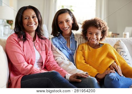 Three generation family female family group sitting on a sofa in the living room smiling to camera, close up