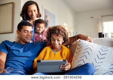 Young family spending time together using a tablet computer in their living room, front view