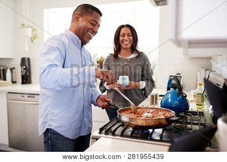 Millennial Hispanic man standing in the kitchen cooking with his partner standing beside him, backlit