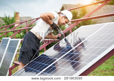 Back View Of Young Technician In Helmet Connecting Solar Photo Voltaic Panel To Metal Platform Using