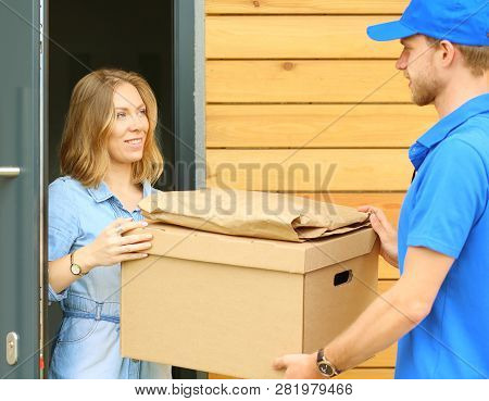 Smiling Delivery Man In Blue Uniform Delivering Parcel Box To Recipient - Courier Service Concept. S