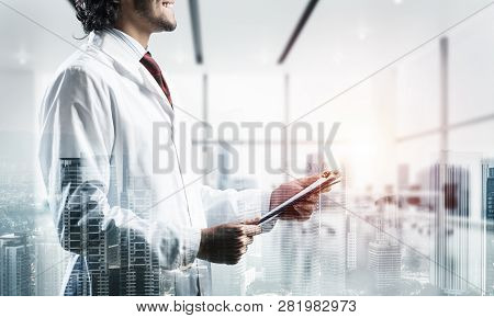Double Exposure Of Confident Doctor In White Sterile Coat Standing Inside Hospital Office And Modern