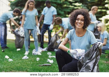 Volunteering, Charity And Clean Environment Concept. Happy Black Woman And Group Of Volunteers With