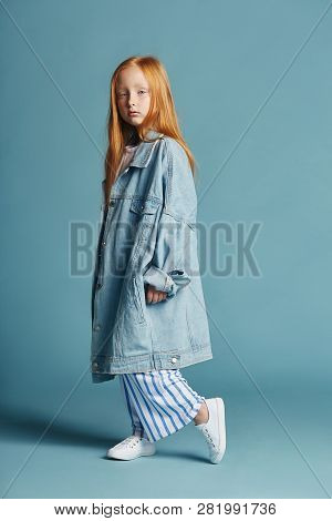 Beautiful Redheaded Baby Girl With Long Hair In A Big Blue Long Denim Jacket. Fashion Clothing, Spri