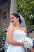 Bride stands in front of church. She has on a strapless gown and is holding her bouquet of white roses. poster