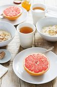 Vegetarian breakfast for two of oatmeal, baked grapefruit and tea. Rustic style. poster