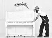 Man with beard worker in helmet and overalls pushes, efforts to move piano, white background. Loader moves piano instrument. Heavy loads concept. Courier delivers furniture, move out, relocation poster