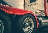Semi Truck Heavy Duty Tires and Chromed Alloy Wheels. Driving in a Heavy Rain Conditions. Modern Truck Tractor Rear Wheels. Automotive Industry. poster