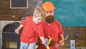 Boy, child cheerful playing with toy saw, learning use tools with dad. Father, parent with beard in protective helmet teaching little son to use different tools in school workshop. Fatherhood concept poster