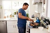 Young adult black man standing in the kitchen cooking on the hob, using a spatula and frying pan, side view, close up poster