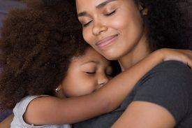 Loving Single Black Mother Hugs Cute Daughter Feel Tenderness Connection