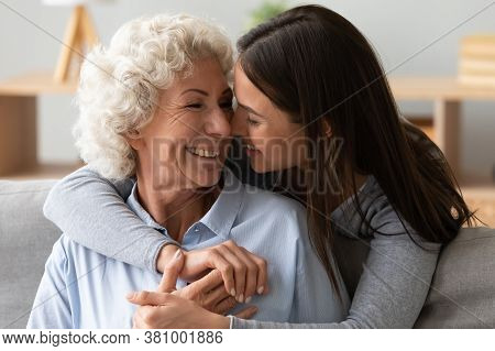 Young Beautiful Woman Cuddling From Back Smiling Mature Mother.