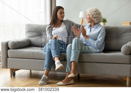 Young Happy Beautiful Woman Talking With Elderly Mom Indoors.