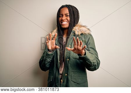 Young african american woman wearing winter parka coat over isolated background disgusted expression, displeased and fearful doing disgust face because aversion reaction. With hands raised