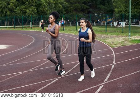 Fitness Classes On The Street. Lovely Girlfriends Run On The Sports Track At The Stadium. Fit, Athle
