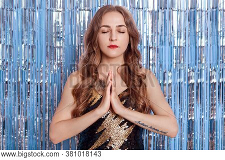 Young Caucasian Woman Posing With Hands Pressed Together In Namaste While Practicing Yoga Against Bl