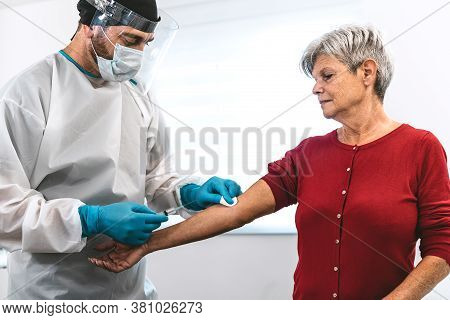 Doctor Doing Medical Injection Syringe Vaccine To Senior Patient In Hospital For Preventing And Stop