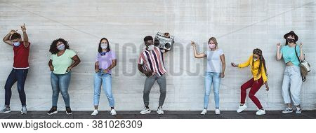 Happy Friends Wearing Face Mask Listening Music With Vintage Boombox Outdoor - Multiracial Young Peo