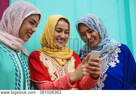 Young Muslim Friends Watching On Mobile Phone Outdoor - Happy Arabian Girls Addicted To New Technolo