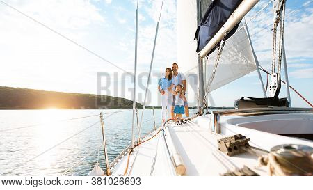 Luxury Vacation. Family Relaxing On Yacht Or Catamaran Enjoying Boat Ride Standing On Deck And Huggi