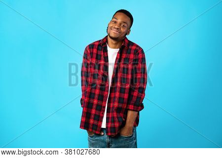 African American Millennial Guy Standing Holding Hands In Pockets Posing On Blue Studio Background,