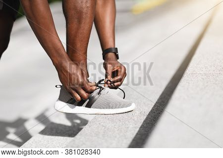 Black Sportsman Tying Shoelaces Before Running, Getting Ready For Jogging Outdoors, Putting Leg At S