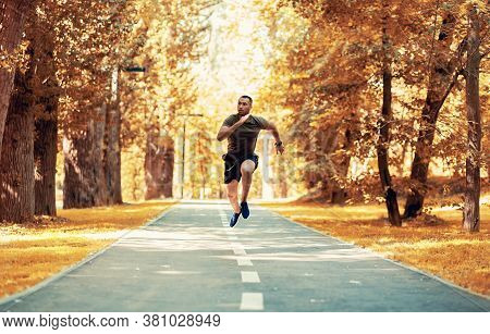 Black Sprinter Training For Race On Jogging Track At Beautiful Autumn Park, Copy Space. Panorama