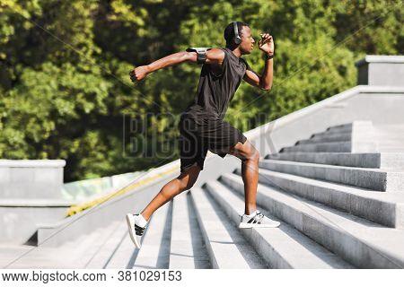 Sport Motivation. Black Male Athlete Running Up On Urban Stairs Outdoors, Enjoying Morning Workout,