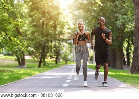Morning Jogging Concept. Motivated Black Couple Running Together In Summer Park, Listening Music In
