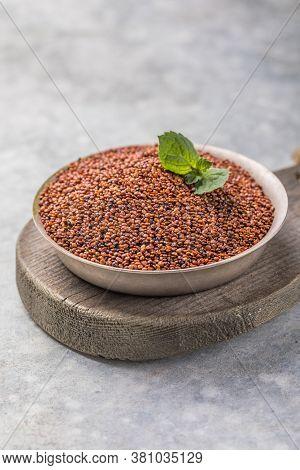 Raw Red Quinoa Seeds (lat. Chenopodium Quinoa) On Plate. Raw Red Quinoa Seeds