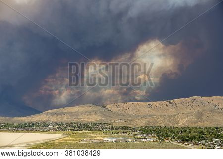 Dense Clouds And Smoke Surround A Hole In The Sky From A Large Wildfire In The Desert Community And