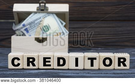 Creditor Word On Cubes With A Chest Of Money Against A Dark Background. Business And Finance Concept