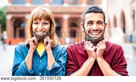 Happy Couple Smiling With Opened Face Mask After Lockdown Reopening - New Normal Relationship Concep