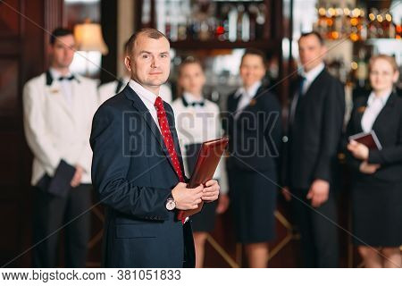 The Interaction Of The Staff. Hotel Or Restaurant Manager And His Staff In Kitchen. Interacting To H