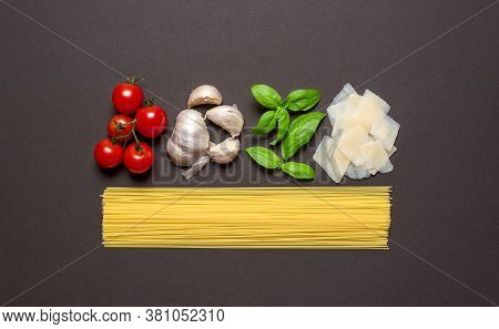 Uncooked Spaghetti And Fresh Ingredients For The Sauce Aligned On A Brown Table, Flat Lay. Above Vie