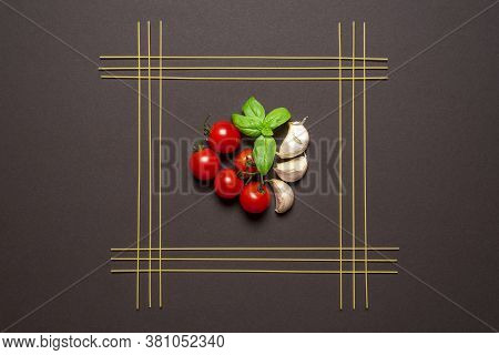 Uncooked Spaghetti Aligned Symmetrically In A Square And The Tomato Sauce Ingredients In The Middle,