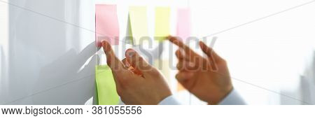 Close-up Of Worker Hand Holding Colorful Papers For Notes With Information. Person Preparing For Con