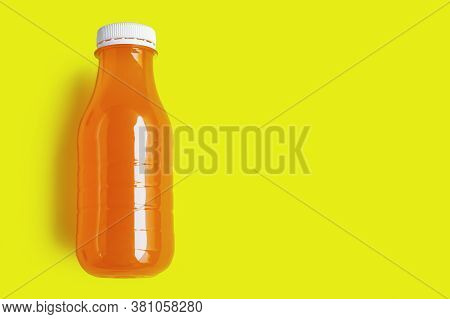 Non-alcoholic Carbonated Drink In A Plastic Bottle On A Yellow Background, The Concept Of Processing
