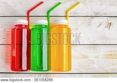 Non-alcoholic Multi-colored Carbonated Drinks With Cocktail Tubes In Plastic Bottles On Wooden Backg