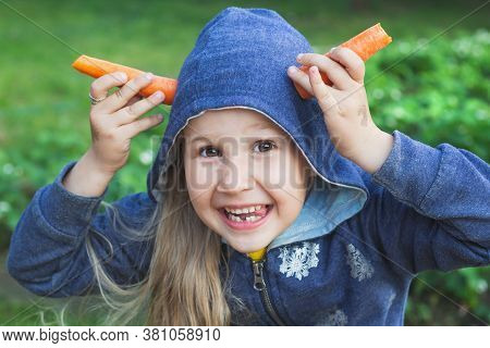 Little Cheerful Girl Shows Horns Or Ears Of Orange Carrots. A Naughty Child In A Blue Hoodie Looks A