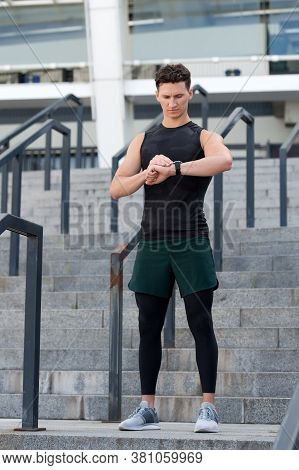 Fitness And Sport. Workout In Gym. A Man Runs Looking At His Pulse Outside With A Smart Watch. Athle