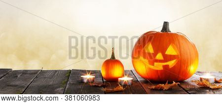 Magic halloween pumpkins and burning candles on golden bokeh lights background