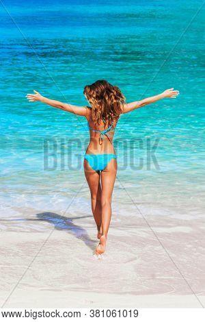 Beautiful woman in bikini walking to blue tropical sea with arms raised