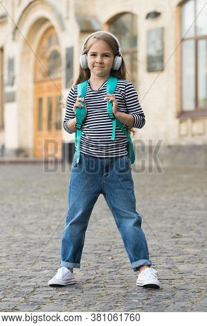 Fit For Her Lifestyle. Happy Child Carry Backpack In Casual Style. Casual Listener Wear Headphones.