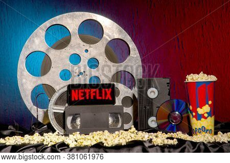 Tula, Russia - August 01,2020: Modern Smartphone With Netflix Logo On Old Film Reels Background