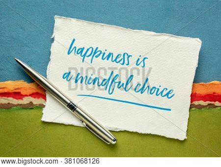 happiness is a mindful choice inspirational note on a sheet of white Khadi rag paper against colorful abstract landscape, mindfulness and personal development concept